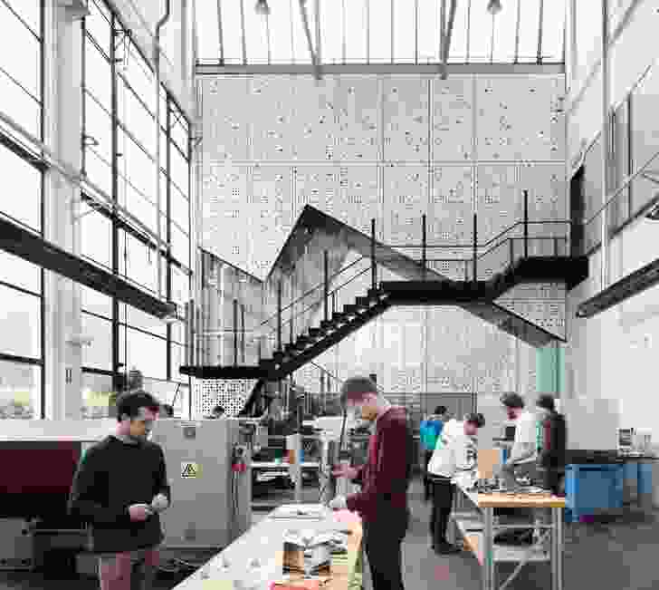A new linkway within the workshop connects the school's two courtyards and accommodates a stair with a viewing platform that looks into the workshop.