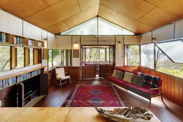 The house responds to the steep, sometimes water-soaked site by standing in the tree canopy.