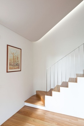 The stair in House 1 sweeps around the back of the living space and leads up to a library.
