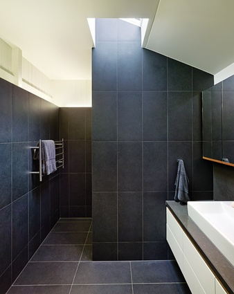 In the main ensuite, wall tiles are stopped short of the ceiling to expose the original timber linings.
