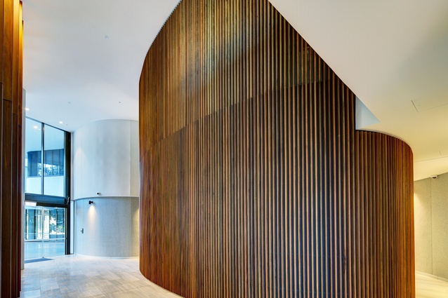 The elliptical form of the towers is echoed within the interior of the podium in the form of curved timber mullion screens encasing the lift cores.