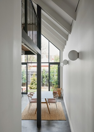 The extant hallway opens to views of the verdant rear garden, beyond the open living space.