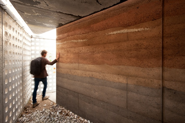 A rammed earth wall in different soil types gives the project a layered, tactile quality.