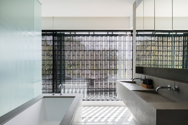 The main ensuite on the upper floor opens onto a monastic stone outdoor shower area.