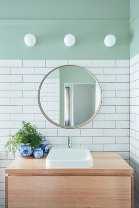 The green paint chosen for the bathroom, also referenced in the kitchen pendant lamp, assists in creating a tranquil space.