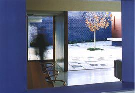 Looking from the kitchen, across the living areas into the main courtyard, with the blue glazed forms of the flat beyond.