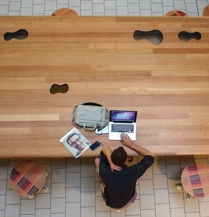 A library user makes use of the building's free wi-fi at the Peanut table.