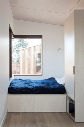In the guest studio, the bed is pushed to the edge of the building and windows extend the space into the garden.