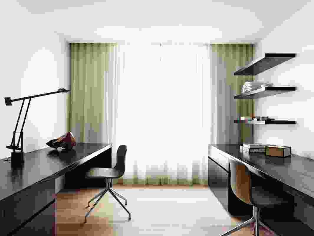 The study features the same light tones as the bedroom and living space, but with warm, dark joinery.