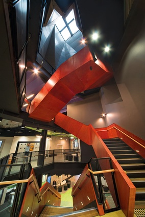 The twisted metal skin skylight adds to the complex spatial matrix of stairs and cross-axes.