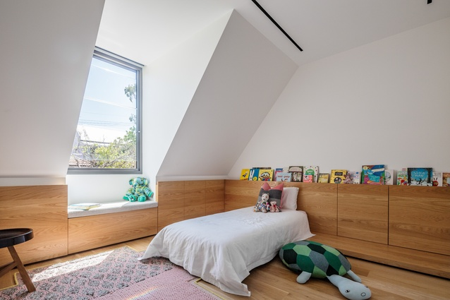 An over-scaled dormer window provides a place to sit and brings light into a child's bedroom.