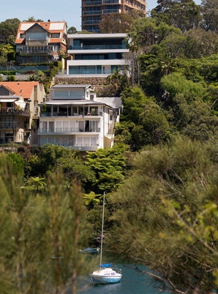 The hill-hugging house viewed from across the bay.