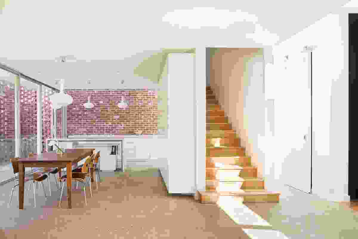 The imperfect red surfaces of the bricks provide a warm counterpoint to the white walls and joinery in the kitchen, dining and living zones. The enclosed stair leads to the bedrooms above.