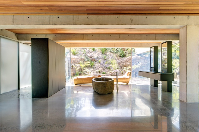 The open-plan sleeping/ bathing space in the private pavilion is wrapped on three sides in glass and circled with earth and stone.