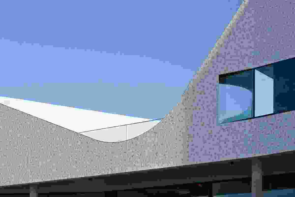 The swooping upstairs parapet: a nod to the  coronet peaks of Le Corbusier's Ronchamp chapel.