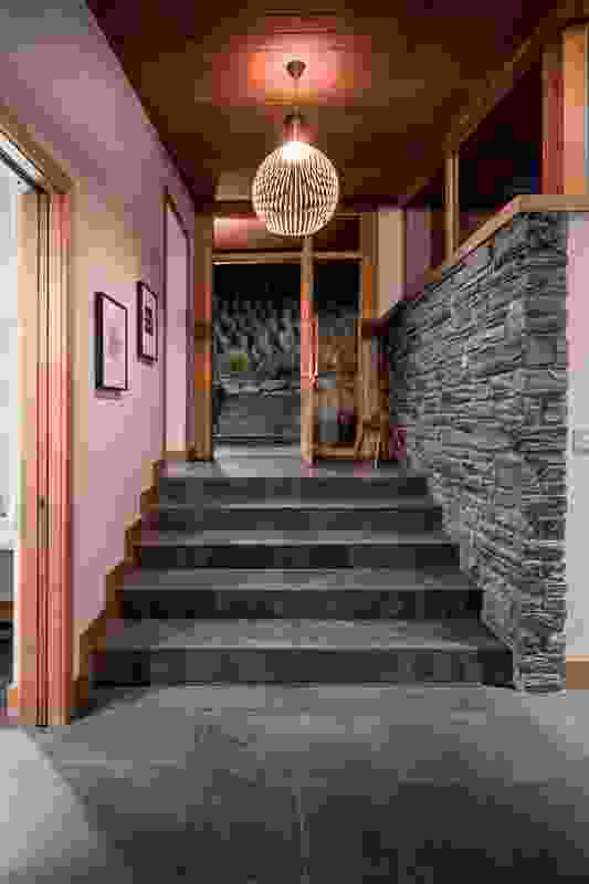 The material palette of timber and stone features inside also, lending cohesion to the internal and external spaces.