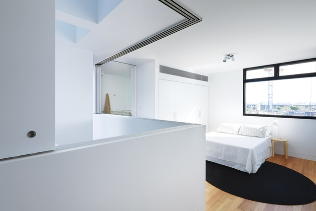 The bedroom on the third floor borrows light from the adjacent void.