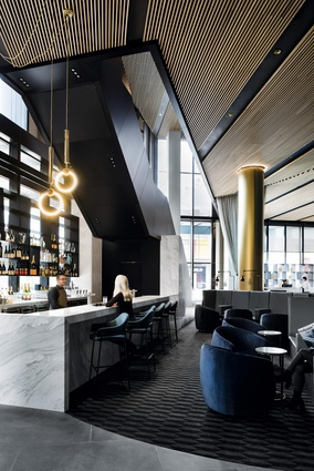 Plush seating in striking blue velvet and teal bar stools line the natural stone bar, housed underneath the layered blackened steel and stone staircase.