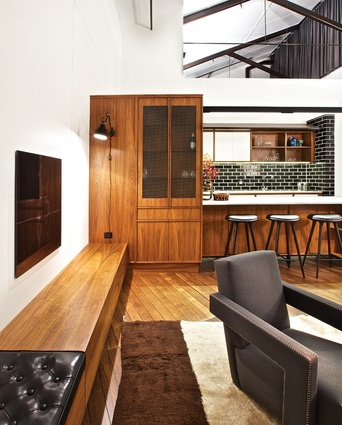 Storage is provided under a low ledge of bench seating in the living space.