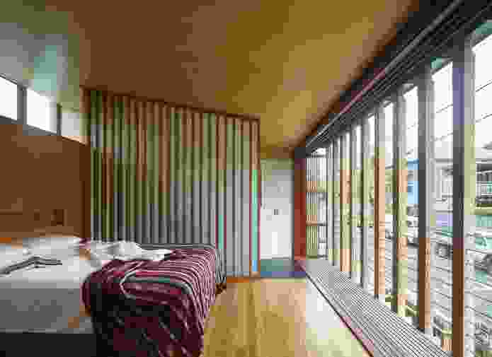 The main bedroom overlooks the street and an outer skin of striated timber encages a narrow strip of balcony.