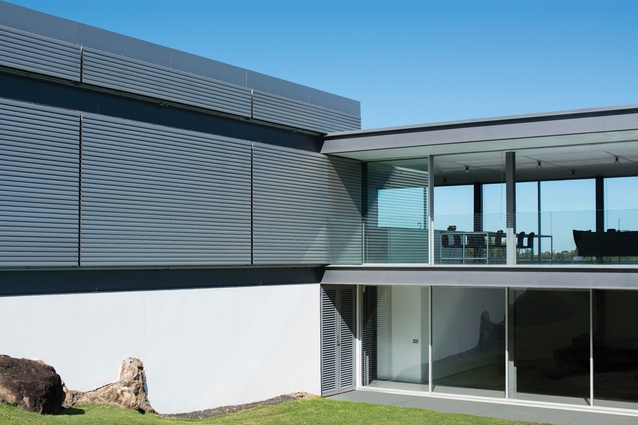 "The house was conceived as an ""open viewing platform,"" with glass and aluminium operable louvres controlling privacy and shading."