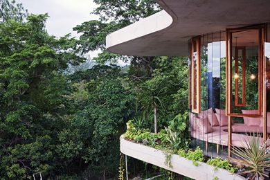 The form of the house is created by two curving concrete slabs (which overlap but aren't the same shape) with glass in between.
