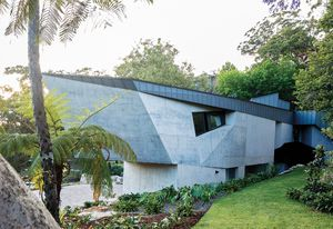 On arrival, visitors encounter a crescent-shaped house with a skin of angular concrete.