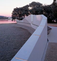 Looking along the east face of Aspect's National Emergency Service Memorial, a thick, long concrete wall above Lake Burley Griffin.