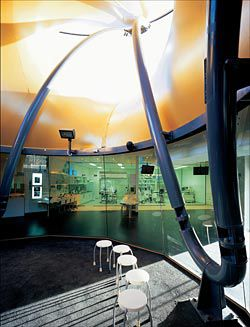 "Inside the ""Impact Experience"" interpretative space at the building's centre, looking across to the visible laboratory and surgical spaces. The gold tensile structure of the ""Costa surface"" is above. Image: Peter Bennetts"