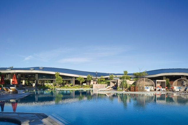 The crescent form of the double curved zinc roof opens up to a large pool, with views to vegetated sand dunes in the distance.