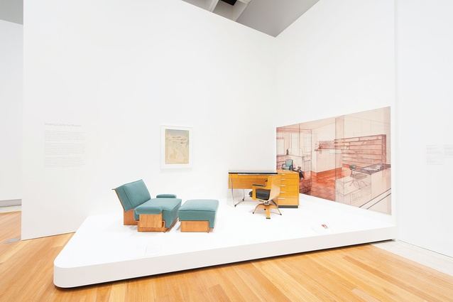 A Schindler armchair and ottoman with Weber's desk and chair set against a super-scaled architectural drawing.