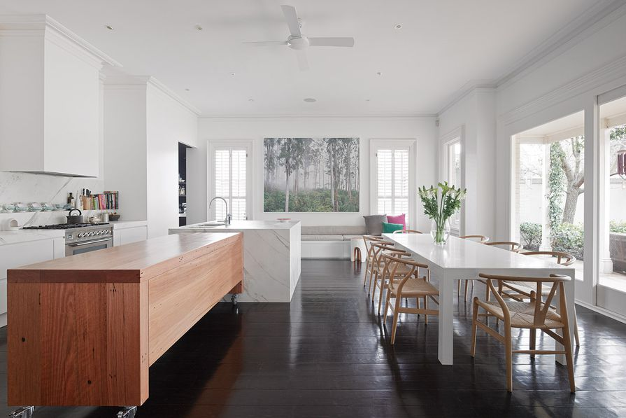 The clean lines of the kitchen and dining area are punctuated by a recycled blackbutt bench. Artwork: Rob Blakers, enlarged image of Tasmanian rainforest. Source: Peter McConchie, Old Growth – Australia's Remaining Ancient Forests (Melbourne: Hardie Grant Books, 2010).