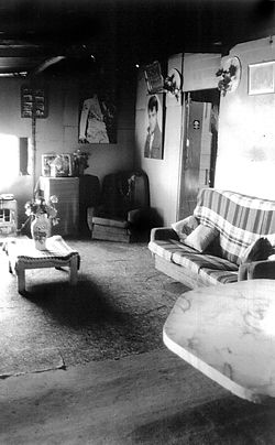 "The interior of Clem and Isabel's ""living room"" was lined with masonite painted sky blue. The floor was a concrete slab flush with the outside and covered with pieces of carpet. A lot of care was taken to keep the room tidy, with the floor swept with a prized stiff broom every day. Elvis music and country and western movies featured strongly in their day-to-day lives and many favourite items are on display. This room is right next to the front door and was occupied as a living and sleeping space depending on the number of inhabitants."