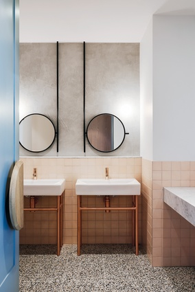 The ladies' bathroom features fine, black-framed, circular mirrors that are reminiscent of 1920s spectacles.