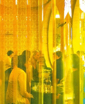 A wall of plastic amber curtain, the type seen in old souvlaki shops, is used to zone spaces.