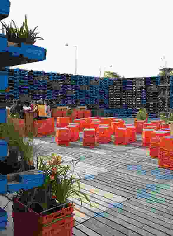 Red plastic crates are used for seating and planter boxes.