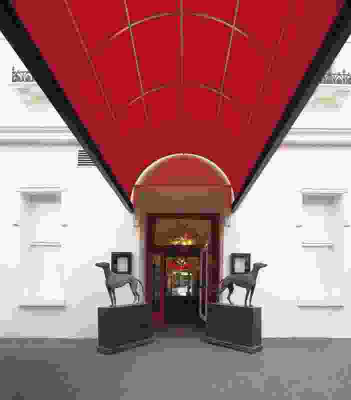 The grand entry with red awning and greyhound sculptures hinting at the sports theme indoors.
