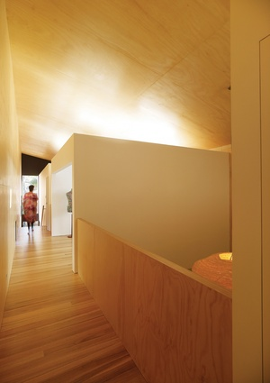 Upper-level bedrooms are expressed as a series of floating boxes in a large, double-height space.