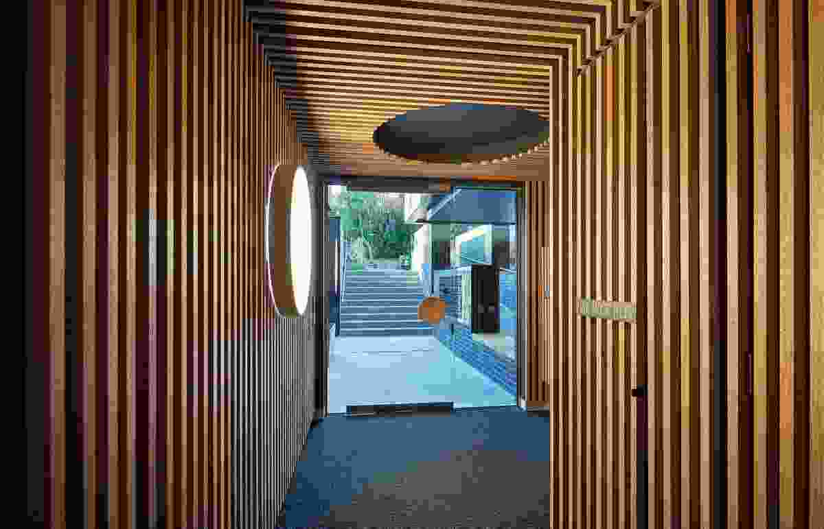 The softly lit entry hallway; the design uses the steep fall on the site to position the pedestrian entry, as well as the vehicle entry, below street level.