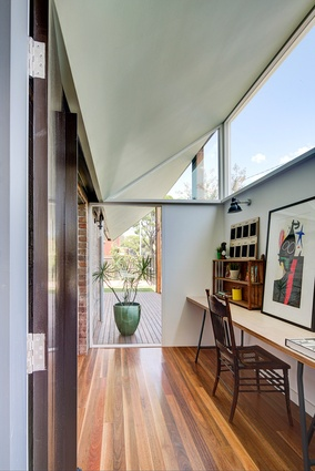 An angular roofline allows light to permeate the entry of the house through clerestory windows.