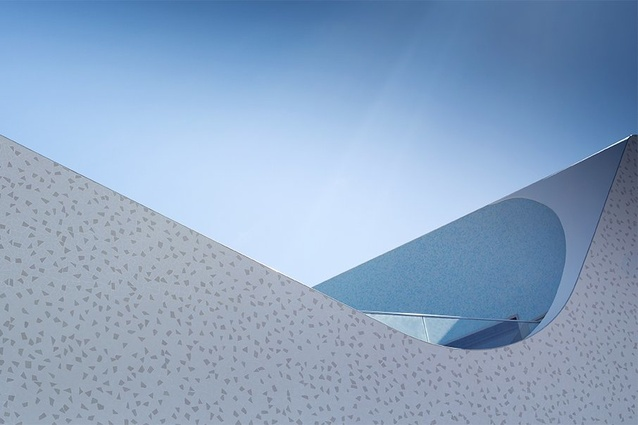 The sculptural swirl of the upper floor parapet references the rolling waves.