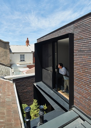 External black steel window surrounds are tapered at angles to block the overlooking of and from neighbours.