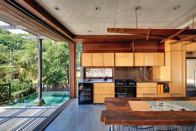 The living level opens to a generous north-facing deck, a lap pool embedded in the forest, the breezeway, the rear courtyard and the bush beyond.