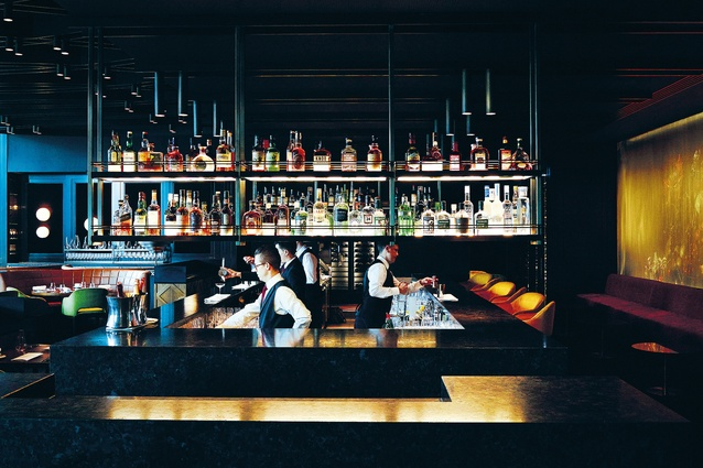 Floor and ceiling play a big part in modulating the space. The bar is set two steps up and the service area is two steps down, so guests are at eye height with the bartender.