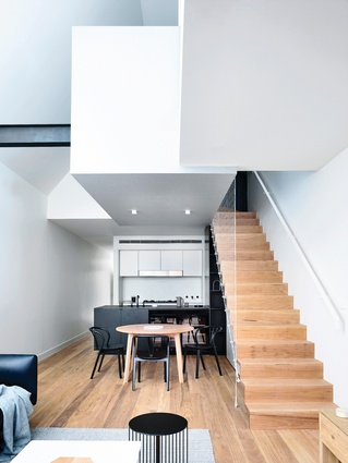 From the ground floor, the second level appears as a sequence of volumes balanced over the kitchen and stair.