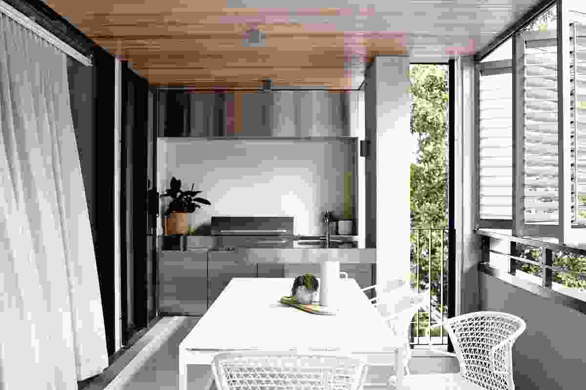 Stretching the width of the building, the main terrace accommodates a dining table and an integrated kitchen.