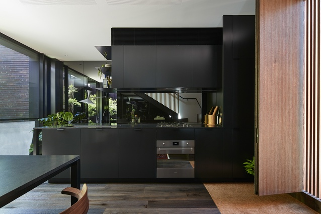 Mirror-lined, black-tinted walls and kitchen splashback extend the visual depth of the tight space.