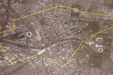 The Hazelwood Open Cut Mine boundary plotted in yellow over an aerial image of central Melbourne at the same scale.