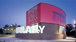 """The playful Elyard Street frontage of the Narellan Library, which provides access to the community and youth services wing of the building. The three-dimensional """"library"""" supergraphic encloses an outdoor area for a cafe.Image:Tyrone Brannigan"""