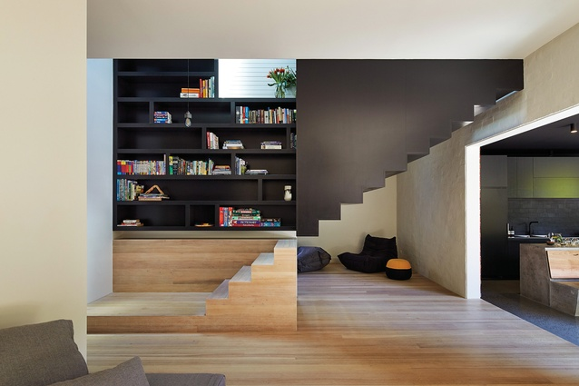 The stair appears to hang from above, and the stair treads wrap up the wall to create an inbuilt joinery unit.